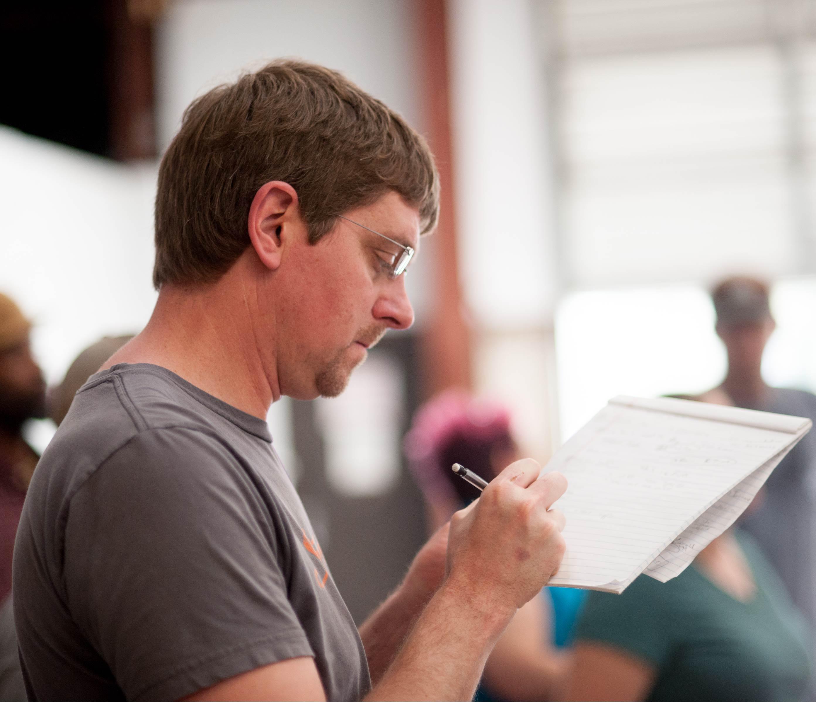 Image of man writing on notepad